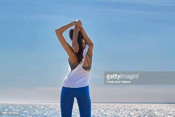 Rear view of young woman arms raised hands behind head stretching