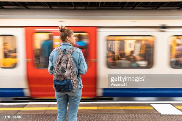 rear view of young woman at subway station with incoming train - london underground stock pictures, royalty-free photos & images