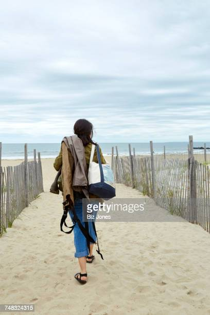 Rear view of young woman carrying sea fishing equipment on beach