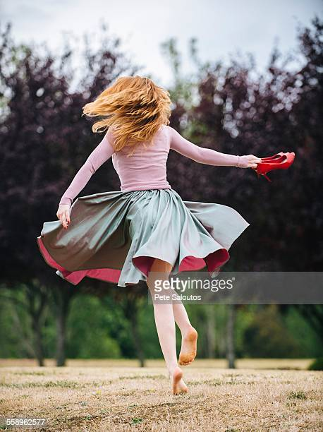Rear view of young woman dancing and twirling and in park