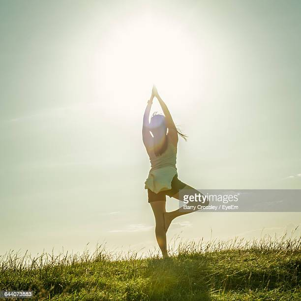 Rear View Of Young Woman Doing Yoga On Field