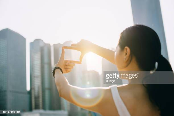 rear view of young woman frames the hong kong city skyline into a finger frame under a sunny sky - lebensziel stock-fotos und bilder