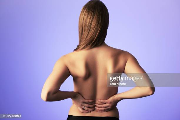rear view of young woman holding back - birthday suit stock pictures, royalty-free photos & images