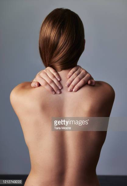 rear view of young woman holding neck - aktfoto frau stock-fotos und bilder