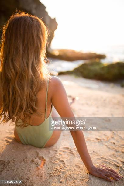 rear view of young woman in bikini sitting at beach against sky during sunset - welliges haar stock-fotos und bilder