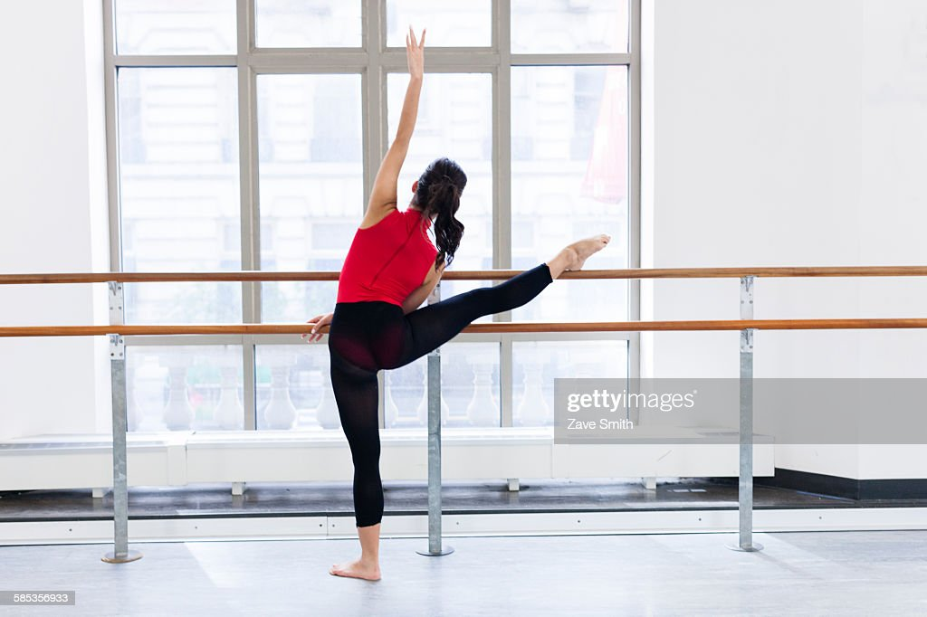 Rear view of young woman in front of window leg raised on barre : Stock Photo