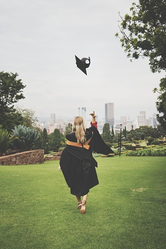 Rear View Of Young Woman In Graduation Gown Throwing Mortarboard While Walking On Grassy Field At Park - gettyimageskorea