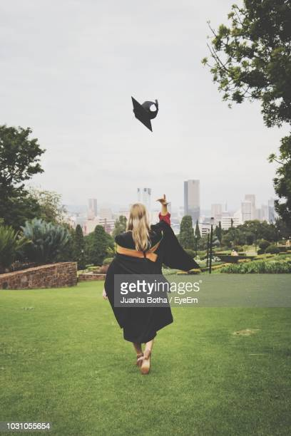 rear view of young woman in graduation gown throwing mortarboard while walking on grassy field at park - mortar board stock pictures, royalty-free photos & images