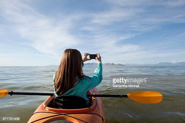 Rear view of young woman in kayak taking photograph, Great Salt Lake, Utah, USA