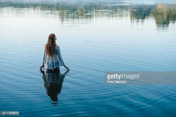 rear view of young woman in lake rippling surface with her fingers - lake auburn stock photos and pictures