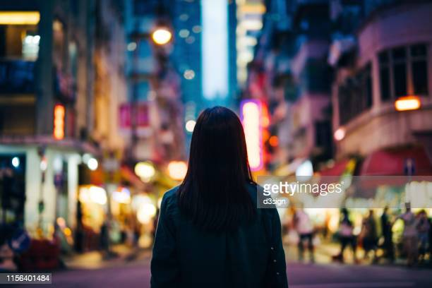 rear view of young woman in the city standing against the illuminated city street at dusk - surrounding stock pictures, royalty-free photos & images