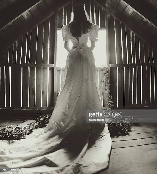 Rear view of young woman in wedding dress on attic