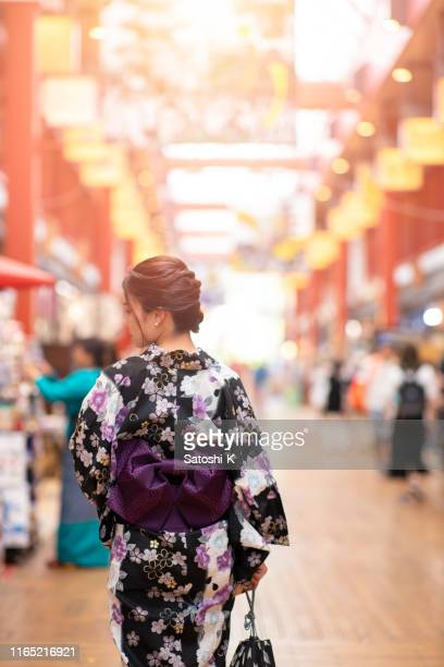 rear view of young woman in yukata walking in traditional japanese shopping street - obi sash stock pictures, royalty-free photos & images