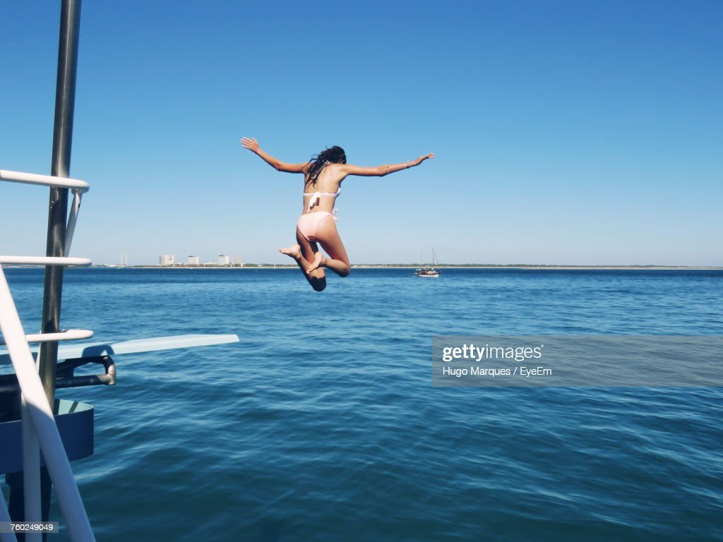 Rear View Of Young Woman Jumping In Sea Against Clear Sky : Stock Photo