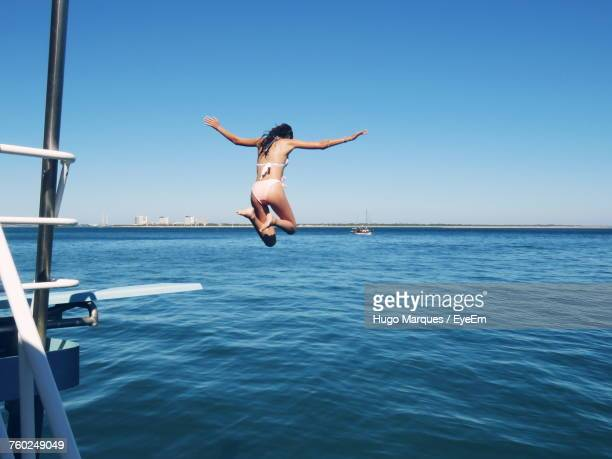 Rear View Of Young Woman Jumping In Sea Against Clear Sky