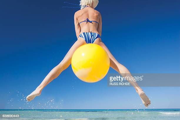 rear view of young woman jumping mid air on space hopper at beach, majorca, spain - hoppity horse stock photos and pictures