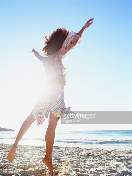 Rear View of Young Woman Jumping on the Beach