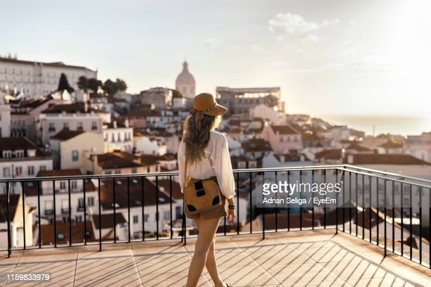 rear view of young woman looking at city buildings against sky during sunset - lissabon stockfoto's en -beelden