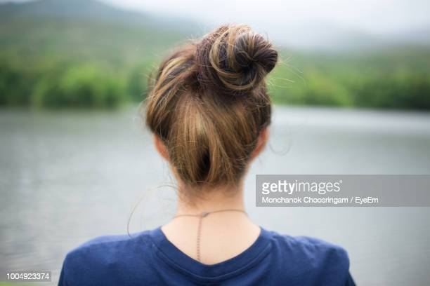 rear view of young woman looking at lake - rodete fotografías e imágenes de stock
