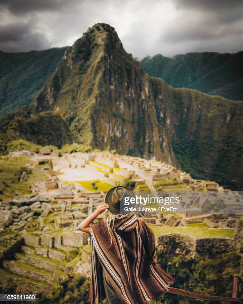 rear view of young woman looking at mountain range while standing against cloudy sky - peru stock pictures, royalty-free photos & images