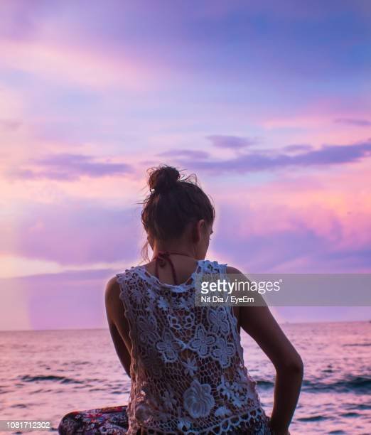 Rear View Of Young Woman Looking At Sea While Sitting On Beach Against Sky During Sunset