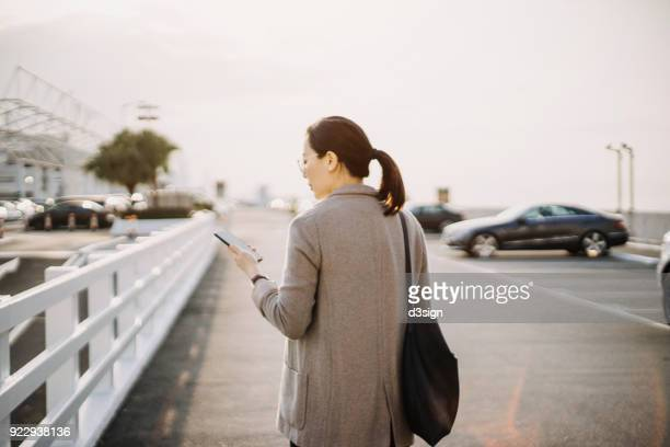 Rear view of young woman looking at smartphone outdoors in city