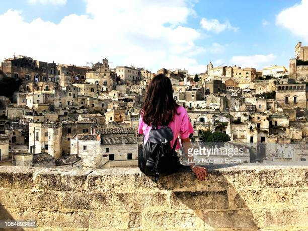 rear view of young woman looking at townscape while sitting on retaining wall against sky - alleen één jonge vrouw stockfoto's en -beelden