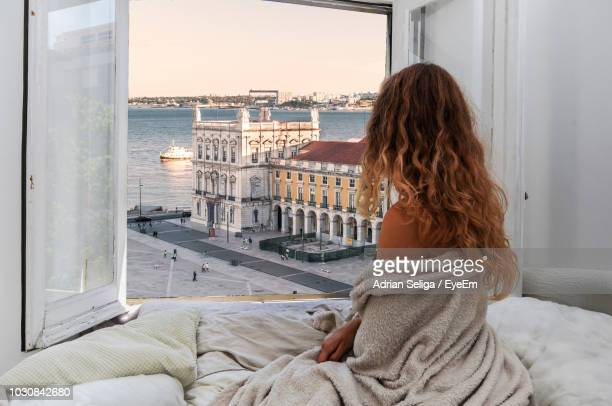 Rear View Of Young Woman Looking At View Through Window While Relaxing On Bed In Hotel