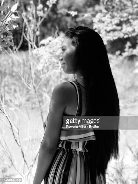 rear view of young woman looking away outdoors - rowena miller stock photos and pictures