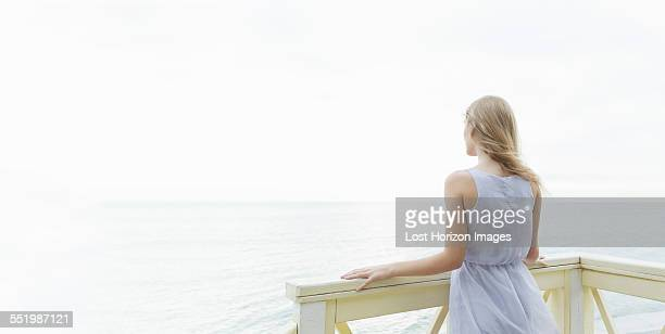 Rear view of young woman looking out to sea from balcony, Miami Beach, Florida, USA