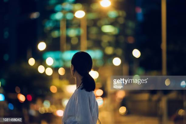 rear view of young woman looking towards illuminated city skyline at night - prosperity stock pictures, royalty-free photos & images