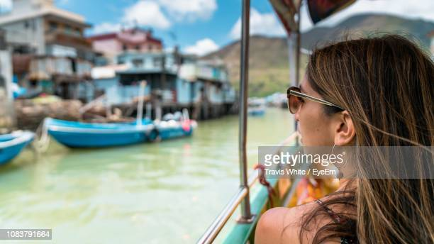 rear view of young woman on boat in canal - lantau stock pictures, royalty-free photos & images