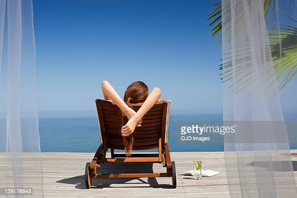Rear view of young woman on deck chair