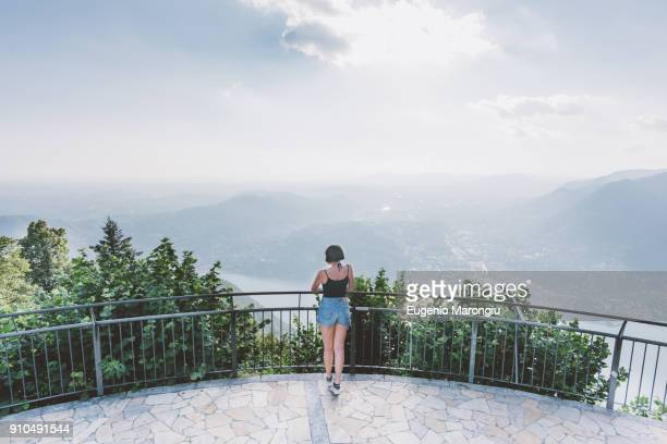 rear view of young woman on viewing platform looking out at lake como, lombardy, italy - alleen één jonge vrouw stockfoto's en -beelden