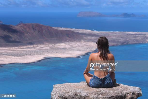 Rear View Of Young Woman Overlooking Sea While Sitting On Rock At Lanzarote