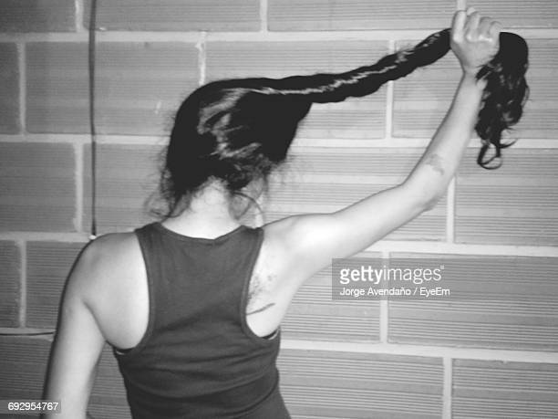 Rear View Of Young Woman Playing With Hair Against Wall