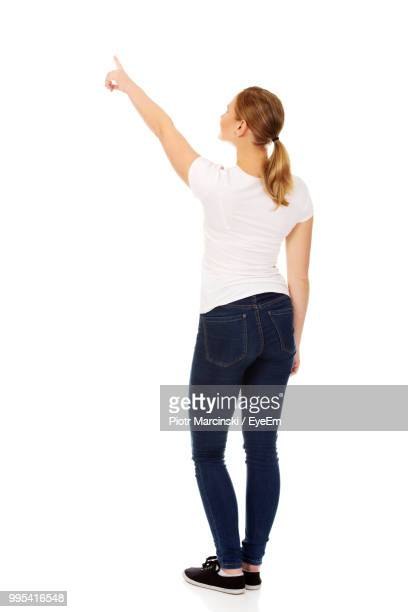 rear view of young woman pointing against white background - stare in piedi foto e immagini stock