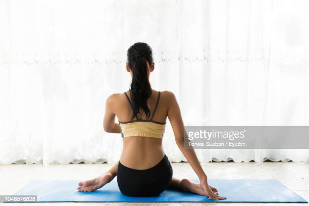 rear view of young woman practicing yoga against curtain at home - torwai stock pictures, royalty-free photos & images