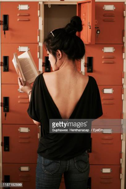 rear view of young woman reading book while standing by locker - バックレス ストックフォトと画像