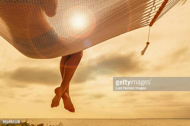 Rear view of young woman reclining on hammock at dusk on Miami Beach, Florida, USA