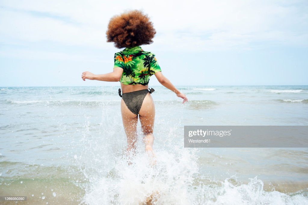 Rear view of young woman running at the beach : Stock Photo