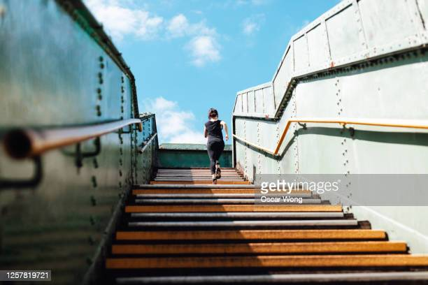 rear view of young woman running upstairs in art district, city downtown - capital cities stock pictures, royalty-free photos & images