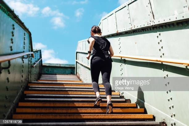 rear view of young woman running upstairs in art district, city downtown - street style stock pictures, royalty-free photos & images