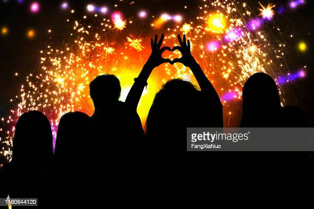 rear view of young woman silhouette making heart shape symbol at firework celebration - celebrities photos stock pictures, royalty-free photos & images