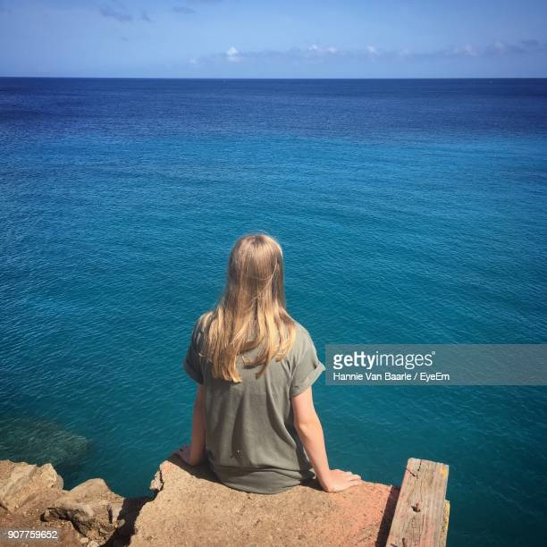 Rear View Of Young Woman Sitting At Sea Shore Against Sky