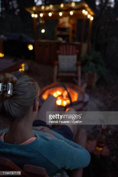 rear view of young woman sitting by fire pit at night - fire pit stock pictures, royalty-free photos & images