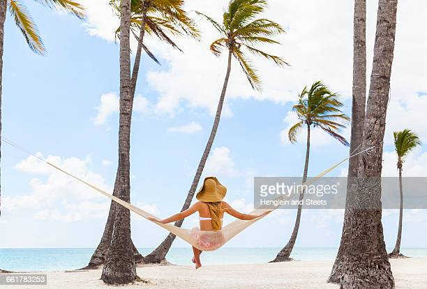 Rear view of young woman sitting on beach hammock, Dominican Republic, The Caribbean