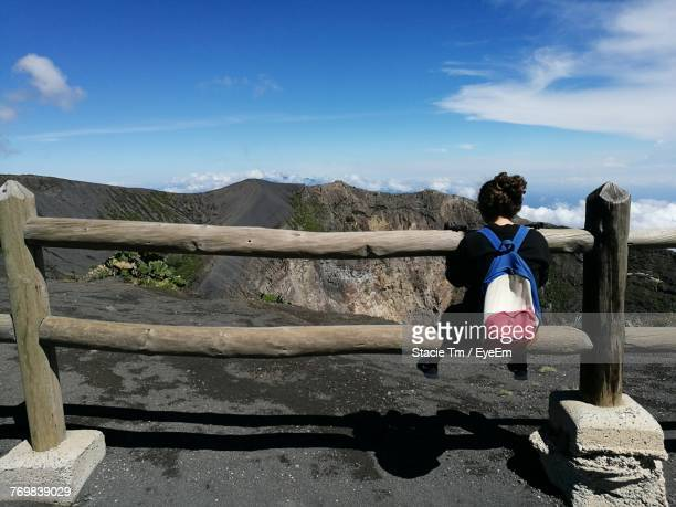 Rear View Of Young Woman Sitting On Fence Against Mountains