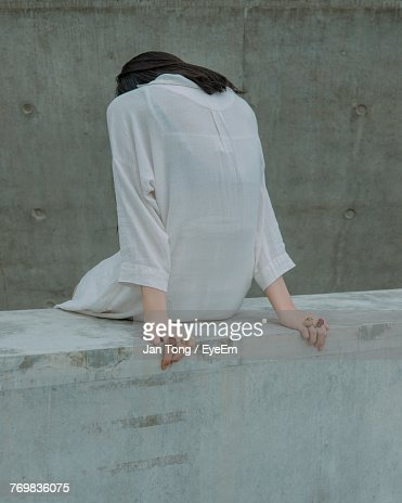 Rear View Of Young Woman Sitting On Retaining Wall