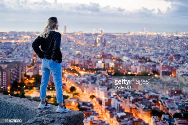 rear view of young woman standing above the city at dawn, barcelona, spain - look back at early colour photography stock pictures, royalty-free photos & images